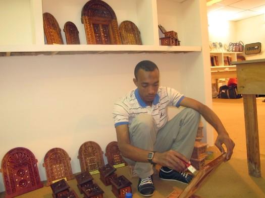 """Mbunifu na mchongaji wa Milango maarufu kama """"Zanzibar Door"""" Bw. Abdul-Rahman akipaka rangi baadhi ya kazi zake katika Maonesho ya Kimataifa ya Sanaa, Ubunifu na Utamaduni yanayofanyika Mascut nchini Oman"""