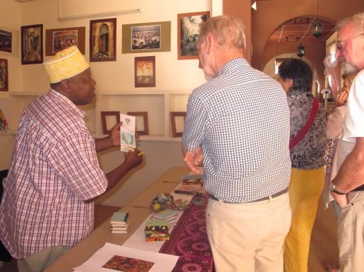 Salum ameir Muchi Mchoraji akiwaonesha baadhi ya kazi zake Wageni waliotembelea Banda la Tanzania katika Maonesho ya Kimataifa ya Sanaa, Ubunifu na Utamaduni yanayofanyika Mascut nchini Oman.