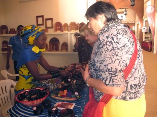 """Mbunifu na Mchongaji """"Big Mama"""" akionesha kazi zake Wageni waliotembelea katika Banda la Tanzania katika Maonesho ya Kimataifa ya Sanaa, Ubunifu na Utamaduni yanayofanyika Mascut nchini Oman."""